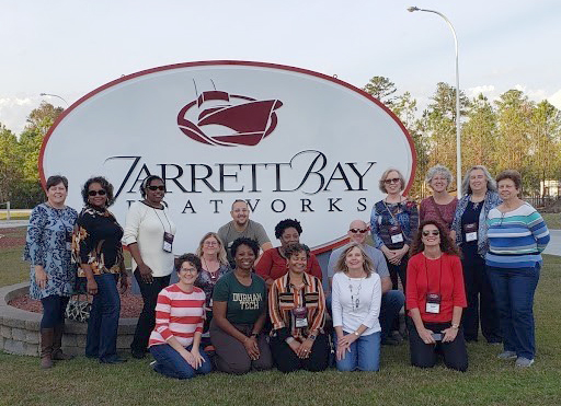 Photo of people in front of Jarrett Bay sign